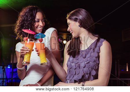 Happy young women having cocktail in bar