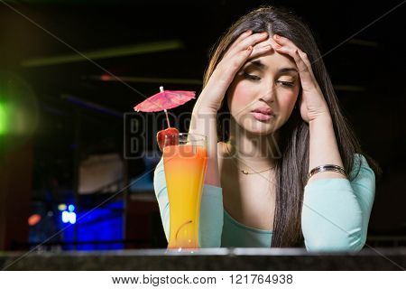 Depressed woman having cocktail drink at bar counter in bar