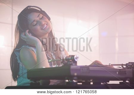 Pretty female DJ listening to the headphone while playing music at nightclub