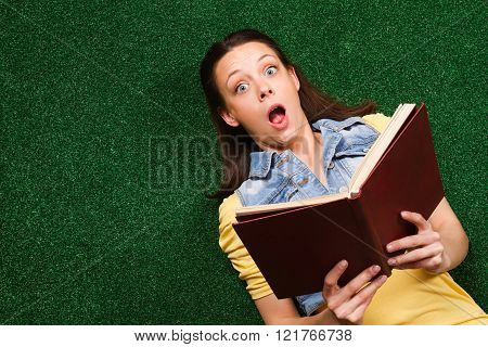 Surprised woman with a book lying on the grass