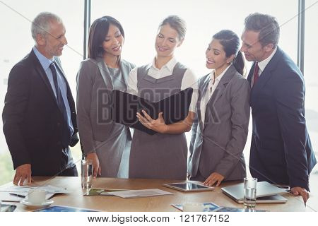 Businesswoman looking at organizer and interacting with team in office
