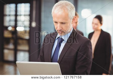 Serious businessman using laptop in office