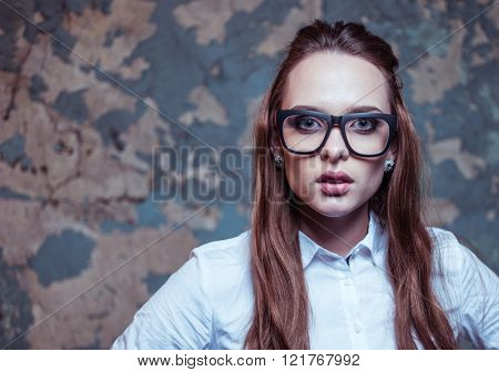 Sexy blonde studentwearing glasses looking at the camera