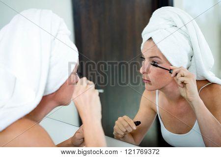 woman wearing a towel on her hair applying mascara