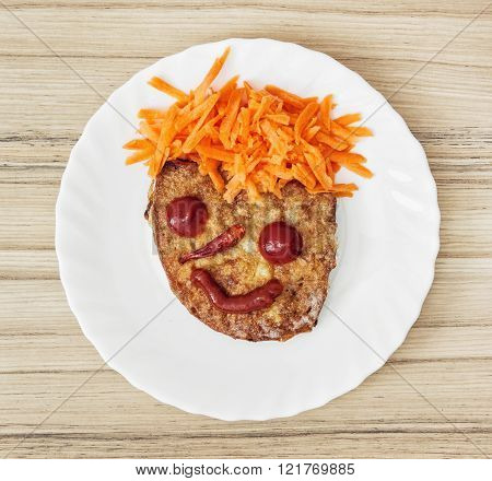 Funny face made of bread, carrot, chilli, tomatoes and ketchup