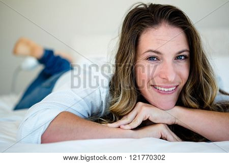 Woman lying on her bed smiling at the camera