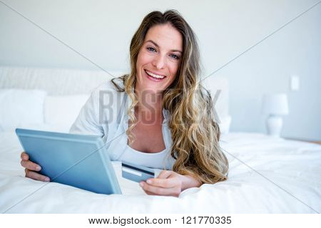 smiling woman lying on her bed on her tablet, holding her credit card