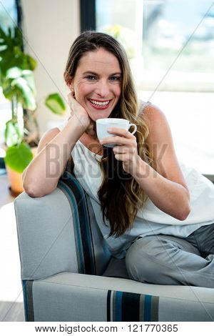 smiling woman, sipping coffee, sitting on her couch