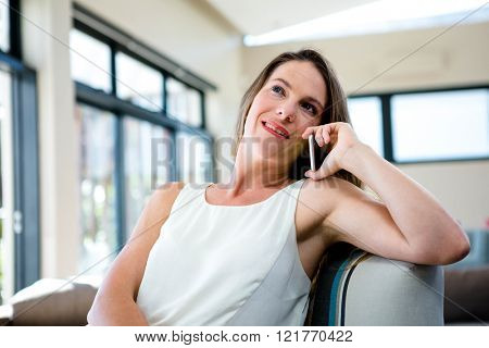 smiling woman, sitting on a couch, talking on her mobile phone