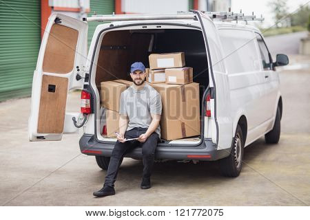 Delivery man holding clipboard while sitting in the cargo area of his van