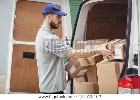 Delivery man holding packages to load his van