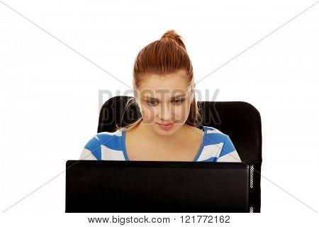 Teenage smiling woman using laptop