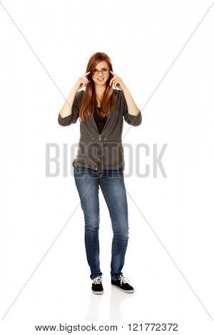 Pretty teenage woman improving glasses