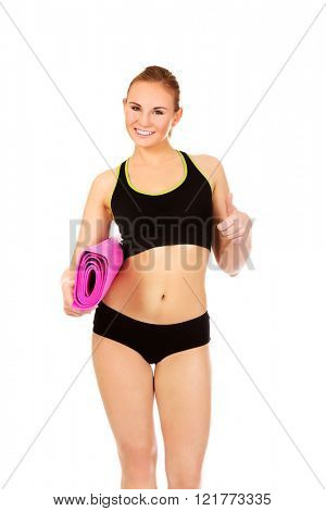 Woman ready for workout with yoga mats and thumb up