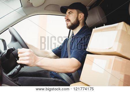 Delivery man driving his van with packages on the front seat