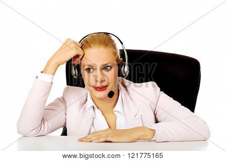 Young woman helpline operator talking through a headphones