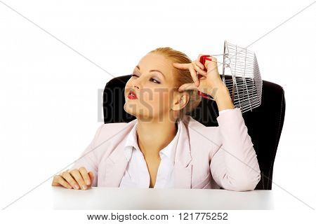 Smile business woman sitting behind the desk and holding small shopping basket