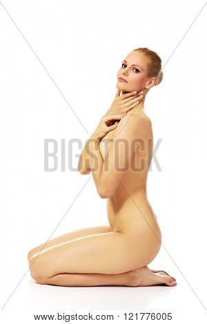 Naked woman kneeling on the floor and touching her neck