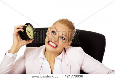 Angry business woman sitting behind the desk and shaking alarm clock