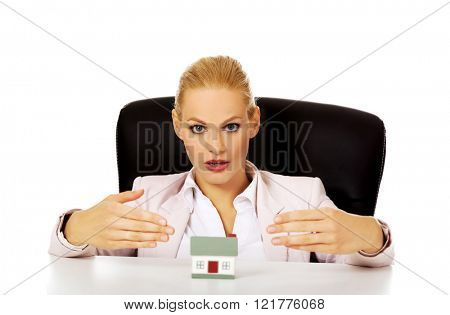 Business woman sitting behind the desk with house model