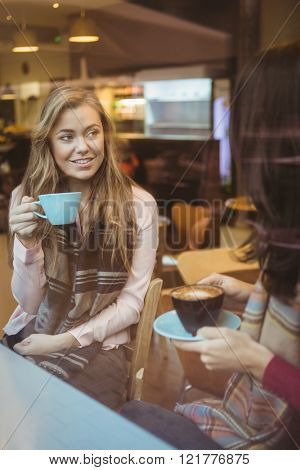 Woman drinking a cup of coffee in cafe
