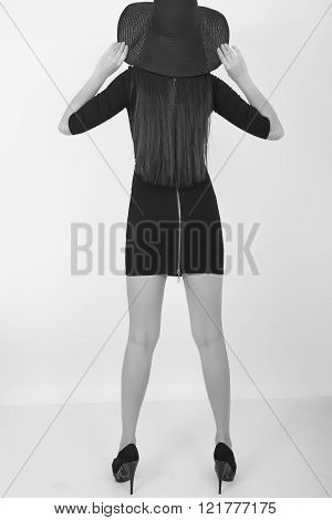 Beautiful young leggy brunette in a little black dress and big black hat, back view. black and white