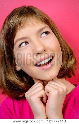 Portrait of a joyful smiling teen girl over pink background.