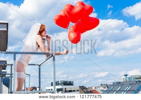 Bride with red balloons on balcony in lingerie