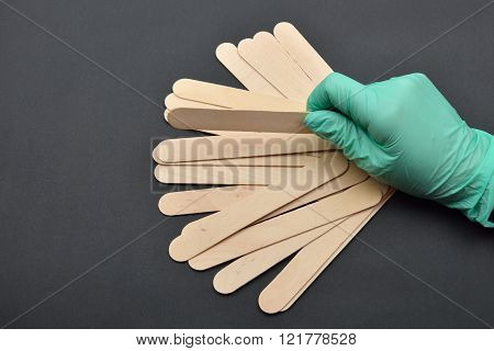 Beauticians Hand With Green Glove Holding Wooden Spatula For Wax Depilation On Black Background. Hai