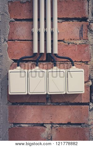 group of four light switches on brick wall