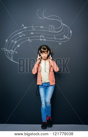 Cute happy teen girl enjoys the music in headphones. Generation. Studio shot.