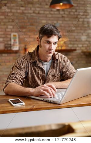 Young man sitting at desk, working with laptop computer.