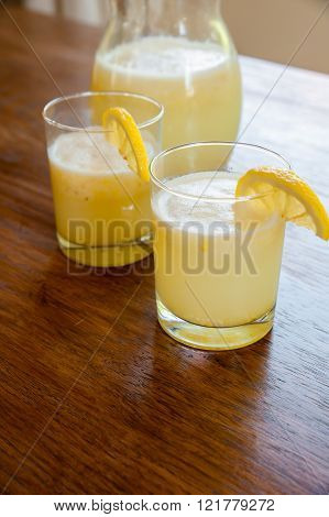 Pitcher and glasses of Homemade lemonade on a garden table