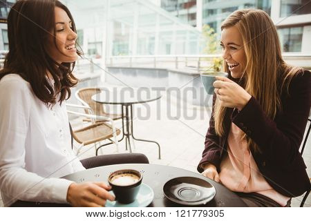 Friends chatting over coffee in cafe