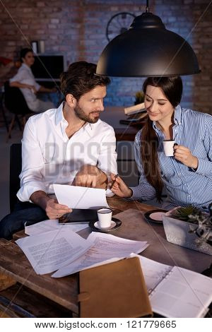 Businesspeople sitting at desk, working together, drinking coffee, smiling.