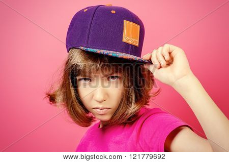 Portrait of a serious teen girl over pink background.