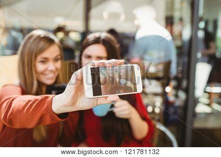Friends taking a selfie in a cafe