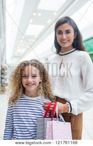 Happy mother and daughter looking at camera in shopping mall