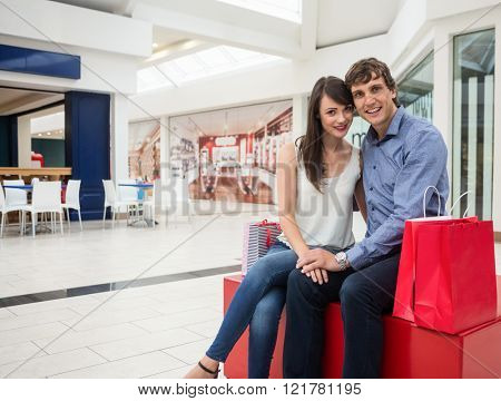 Portrait of happy couple sitting in shopping mall