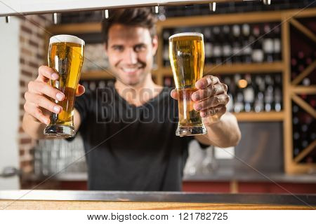 Handsome barman holding a pint of beer in a pub