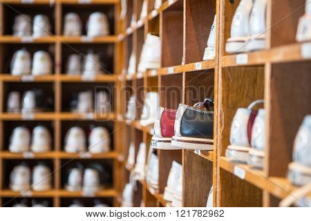 Characteristic leather bowling shoes assorted by size in wooden shelves in a bowling alley.
