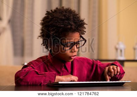 Afro boy using wireless keyboard.
