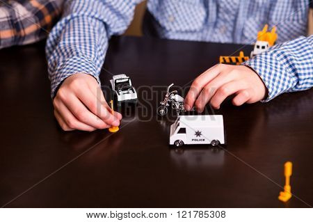 Kid playing with toy cars.