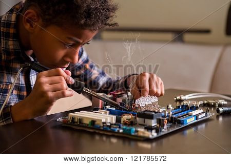 Afro boy fixing motherboard.