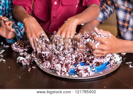 Three children's hands smash cake.