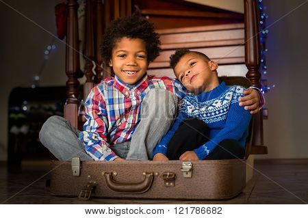 Smiling kids sit inside suitcase.