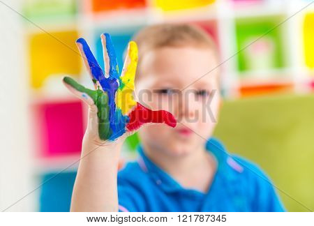 Portrait of cute happy boy with colorful painted hands