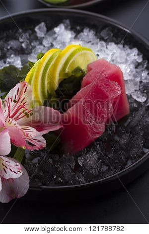 Tuna Sashimi With Ice On A Black Plate