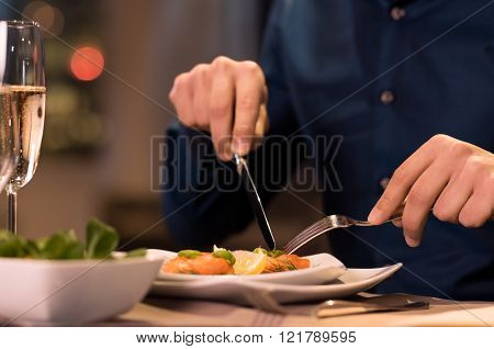 Close up of a male hands cutting and eating delicious salad with knife and fork at restaurant. Man enjoying meal at a restaurant. Close up of a plate of salmon fillet at luxury restaurant.