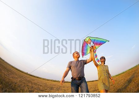 Happy Couple In Love With Flying A Kite